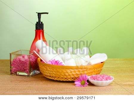 Hotel amenities kit in basket on wooden table on green background