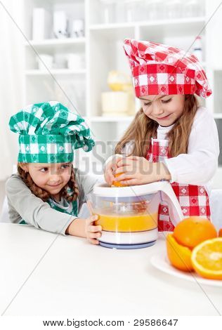 Little girls making fresh orange juice in the kitchen - healthy life education