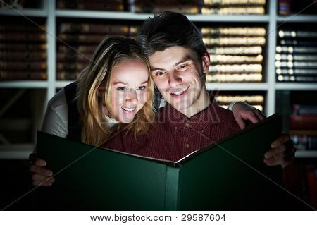 Two young student girl and man reading glowing magic book in a library