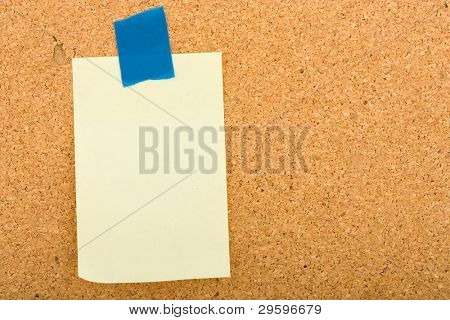 blank sticker glued blue ribbon to a cork board
