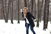 stock photo of snowball-fight  - Outdoor winter portrait of a beautiful happy blond young woman in a snowball fight in the woods - JPG