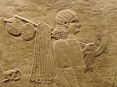 stock photo of babylonia  - Ancient Assyrian wall carvings of men with long hair