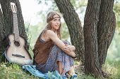 Young Hippie Woman Sitting Near A Tree In The Forest poster