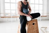 Sweaty Fit Man Sitting On Box And Hold Towel In Hand After Intense Cross Workout. Fitness Athlete Re poster