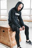 Portrait Of Perspiring Athlete Sitting On Box After Intense Workout At Gym. Tired Fit Man Wearing Ho poster