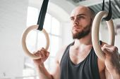 Close Up View On Male Gymnast Doing Workout On Gymnastics Rings In Cross Gym. Fit Athlete Exercises  poster