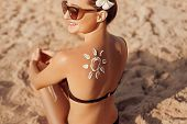 Woman Applying Sun Cream  On Tanned  Shoulder In Form Of The Sun. Sun Protection.sun Cream. Skin And poster
