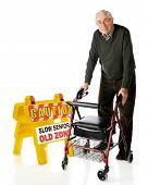Постер, плакат: Старший мужчина счастливо прохождения знак «Осторожно медленно старший» с его wheeling Уокер На белой bac