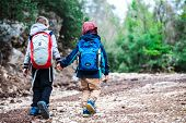 Two Boys With Backpacks Are Walking Along A Forest Path. The Brothers Walk Together In The Park. Two poster