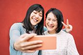Asian Mother And Daughter Taking Photo Selfie With Mobile Smartphone Outdoor - Happy Chinese Family  poster