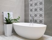 Modern Bathroom Interior Design With White Stone Bathtub, Grey Tiles Wall, Ceramic Flowerpot With Gr poster
