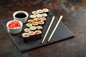 Japanese Sushi Rolls Served On Stone Slate On Dark Background. Sushi Rolls, Maki, Pickled Ginger And poster