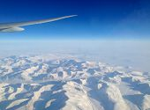 View Of The Snow Mountains And Glaciers Of Greenland From An Airplane Window On A Flight From New Yo poster