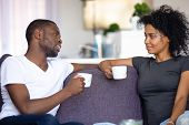 Satisfied African American Couple Talking, Drinking Coffee At Home poster