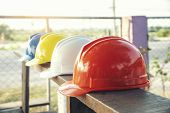 Safety Helmet (hard Hat) For Engineer,safety Officer Or Architect,place On Old Wooden Floor.multi Co poster