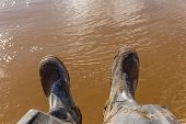 Legs Of A Fisherman Sitting In Dirty Rubber Boots On The Bank Of The River With Dirty Water In The B poster