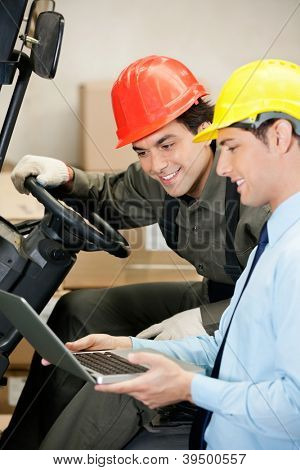 Young male supervisor and forklift driver using laptop at warehouse