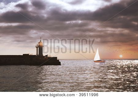 boat in the sea at sunset and lighthouse