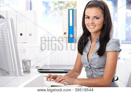 Pretty secretary sitting at desk, typing on computer, smiling, looking at camera.