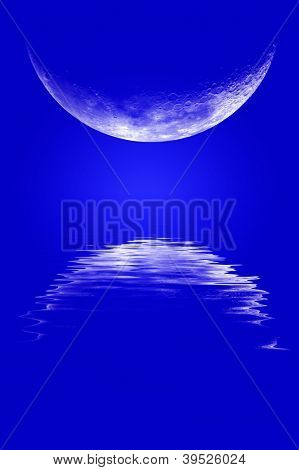 Moonrise over water with reflection and blue sky