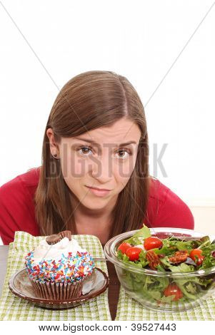 Woman unhappy about a choice of fruit or cupcake