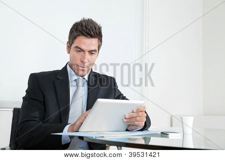 Handsome young businessman at desk with digital tablet and coffee cup in office