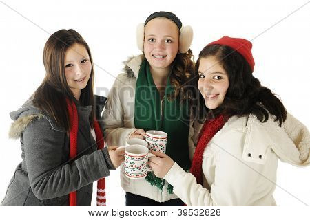 Three tween girl in their winter wear making a toast with holiday mugs.  On a white background.