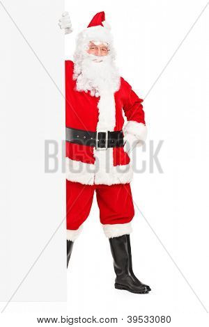Full length portrait of a Santa Claus posing next to a blank billboard isolated on white background
