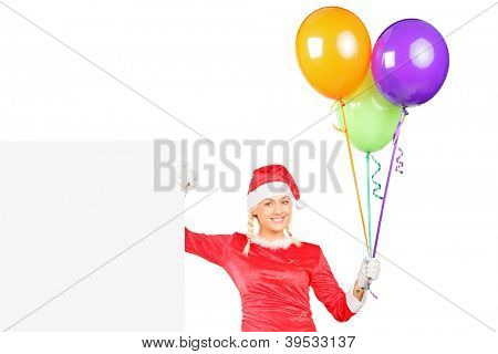 A sexy female in santa costume holding balloons and standing next to a blank billboard