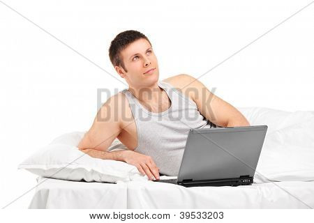 A young thoughtful male lying on a bed and working on a laptop isolated on white background