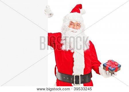 A happy Santa claus standing next to a blank billboard and holding a gift isolated on white
