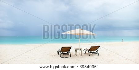 Two chairs under umbrella on stunning tropical beach in Turks and Caicos