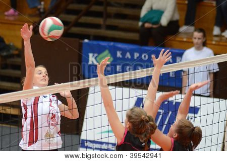 KAPOSVAR, HUNGARY - OCTOBER 14: Zsanett Pinter (L) in action at the Hungarian I. League volleyball game Kaposvar (white) vs Nyiregyhaza (black), October 14, 2012 in Kaposvar, Hungary.