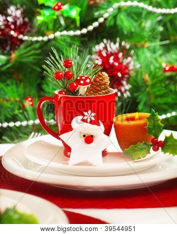 Picture of luxury festive table set, romantic candle with red tea cup and little Christmas decoration on white plate, green spruce tree decorated with beautiful toys, holiday dishware, New Year eve