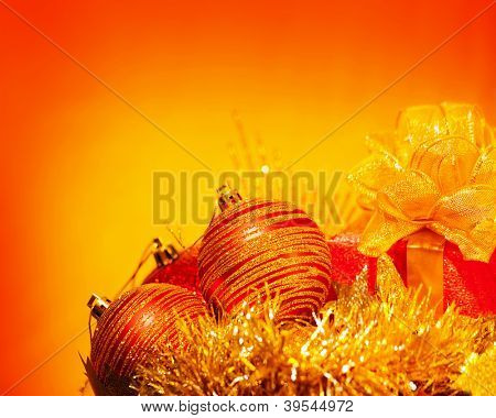 Image of Christmas holiday still life isolated on orange background, red decorative baubles, New Year present with golden ribbon bow, Christmastime decoration, beautiful holiday greeting card