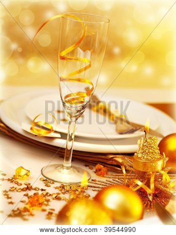 Picture of luxury festive table setting, closeup image of beautiful white utensil decorated with golden shiny balls and candle on blur glowing background, New Year eve, Christmas holiday