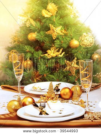 Photo of romantic Christmastime dinner, luxury New Year table setting, gorgeous decorated Christmas tree by golden toys of stars, bubbles and angel, two glass for champagne, holiday still life