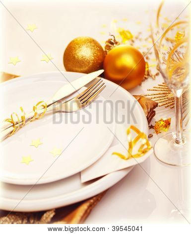 Photo of luxury Christmas table decoration, white plate with knife and fork, glass for wine, traditional New Year holiday table setting with golden bubble decor, happy Christmastime celebration