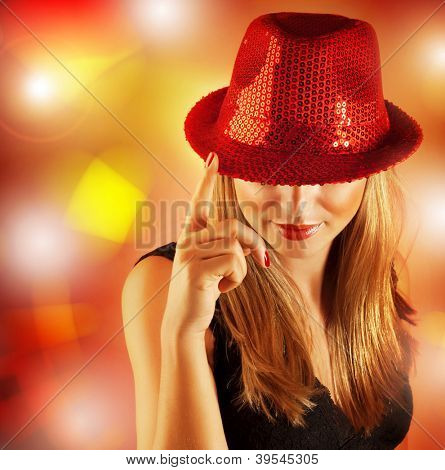 Picture of beautiful woman wearing red hat covered shiny rhinestones and singing on stage in fashionable nightclub, blond girl posing on colorful glowing background, Christmas party