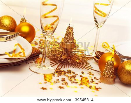 Picture of Christmas romantic table setting, two glasses for champagne adorned with golden ribbon, beautiful little candle, gold shiny bauble, holiday dinner in restaurant, New Year party