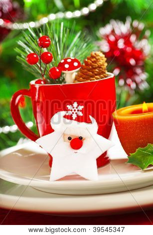 Picture of luxury Christmastime table decoration, red coffee cup decorated with Santa Claus star, yellow candle and berry twig, beautiful white dinnerware on Christmas tree background, New Year party