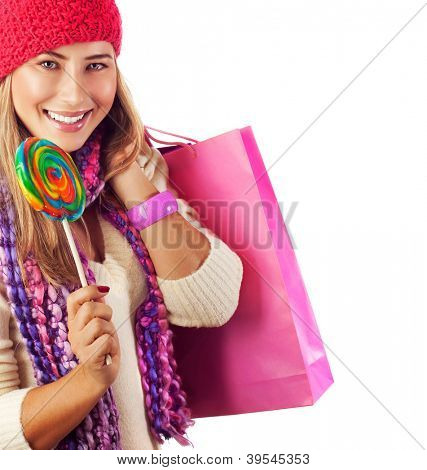 Picture of pretty woman with colorful bonbon and pink present bag isolated on white background, happy woman holding shopping bag and lick sweet candy, red warm hat, Christmas sale, New Year gift