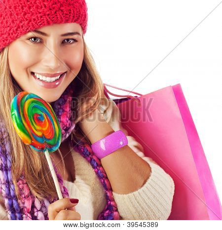 Image of nice blond girl wearing warm winter red hat and eating tasty sugar candy, sweets shop, Christmas present bag, stylish accessories, New Year goody-goody, christmastime holidays