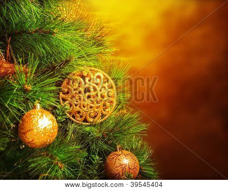 Photo of traditional Christmas tree isolated on brown grunge background, green fir decorated with golden bubbles toy, happy New Year greeting card, adorned pine tree at home, winter holidays