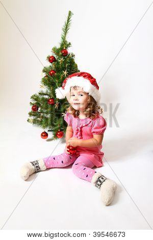 Sweet Baby With A Red Ball Cap Of Santa Claus And Christmas Tree Isolated On White Background