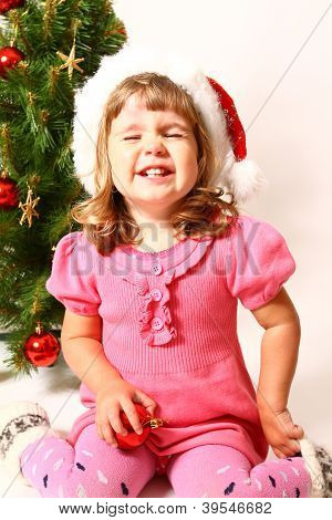 Laughing Baby Sitting Near New Year Or Christmas Tree Isolated On White Background