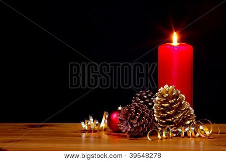 Still life photo of a Christmas candle burning bright with gold pine cones and ribbon plus a red bauble, copy space on the black background to add your own text.