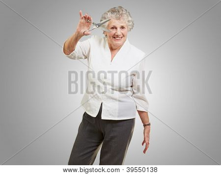 Senior woman holding scissors isolated on gray background
