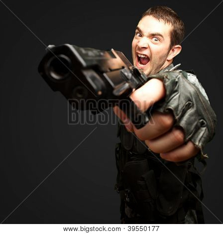 Angry Soldier Holding Gun against a black background
