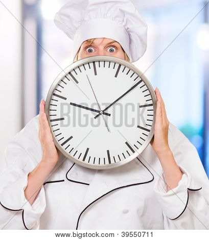 worried chef hiding behind a clock against an abstract background